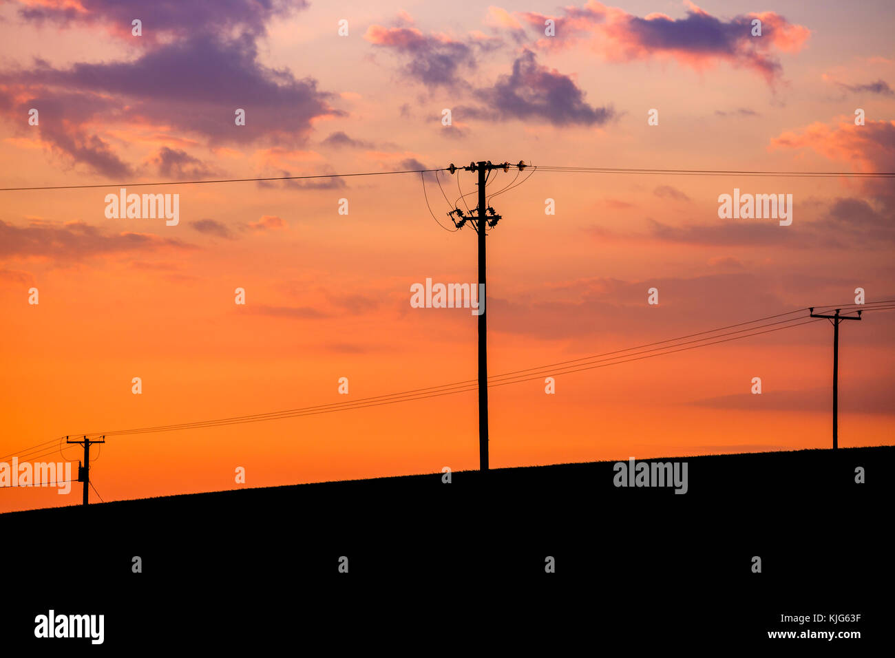 Powerlines and telphone wires against a sunset in Ayr, Scotland, UK. - Stock Image
