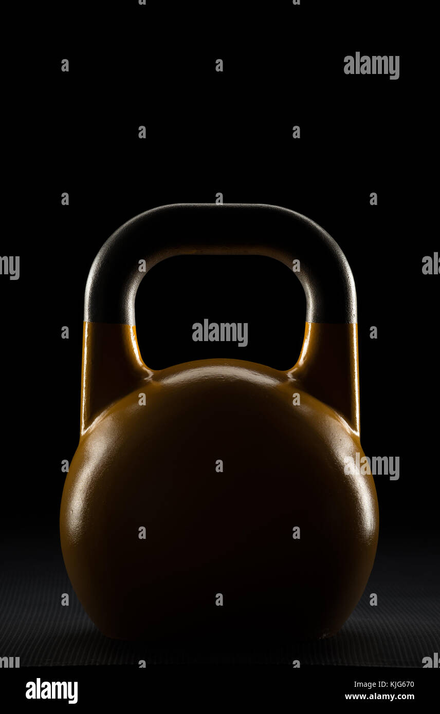 Backlit yelow competition kettlebell silhouette on a black background with text / writing / copy space on and above - Stock Image