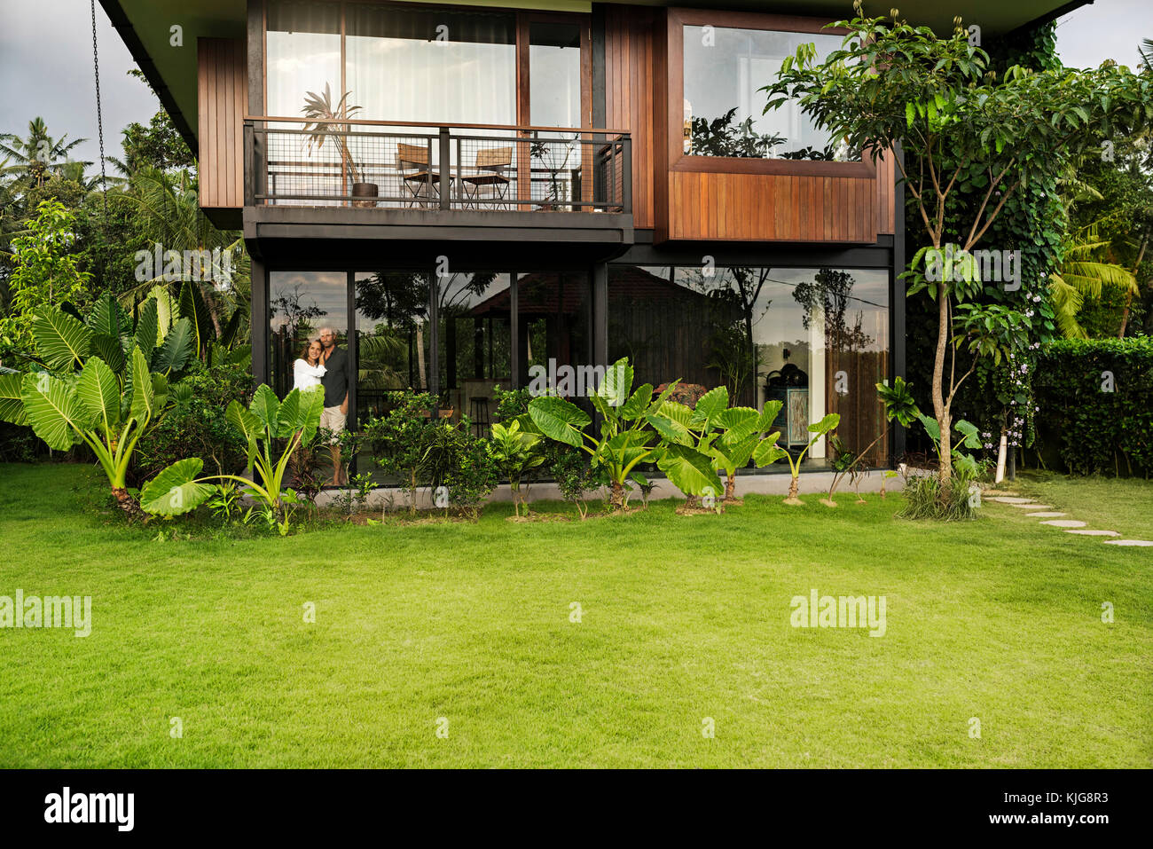 Garden View Of Couple Standing In Modern Design House Surrounded