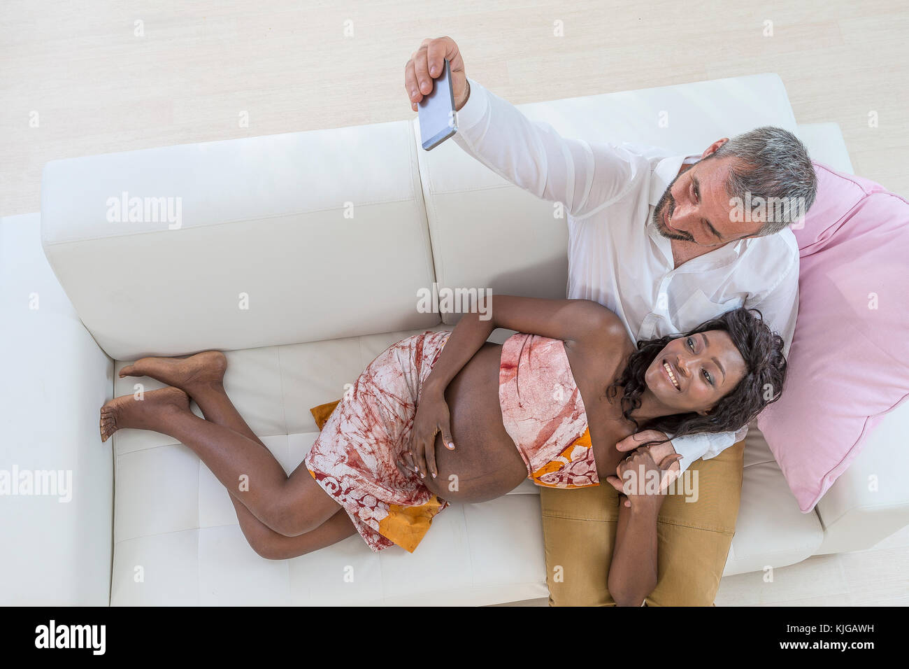 Cute pregnant couple taking a selfie laying on the sofa at home, living room - Stock Image