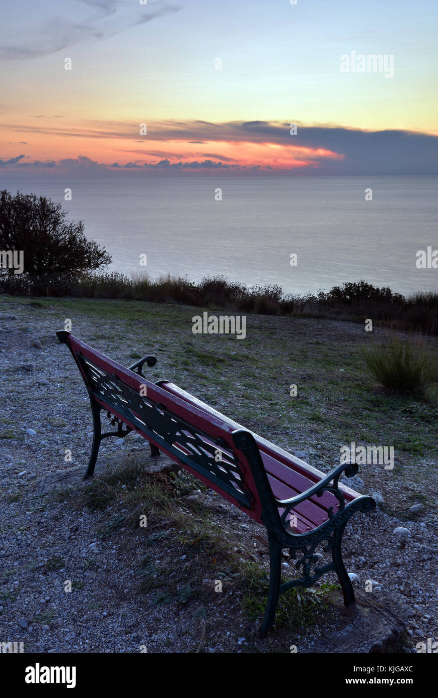 a cast iron an wooden bench on the cliiftop at Paliokastitsa on the Greek island of Corfu at sunset with a calm - Stock Image
