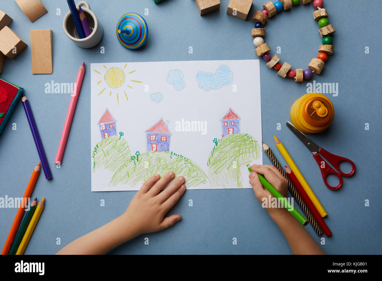 Child drawing landscape with houses - Stock Image