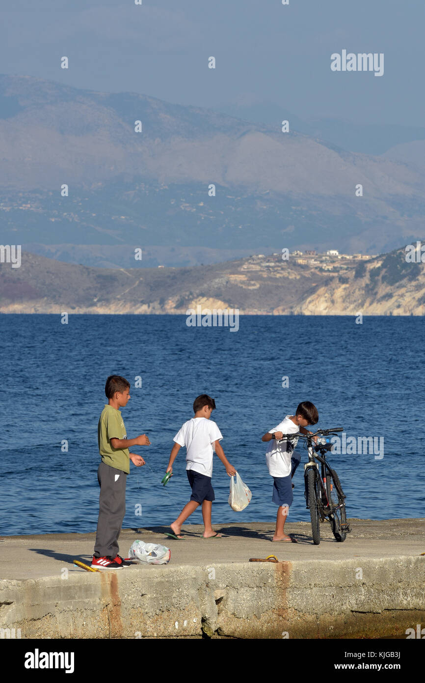 Three young boys or children playing at the quayside or harbour wall fishing with a cycle and having fun in the - Stock Image
