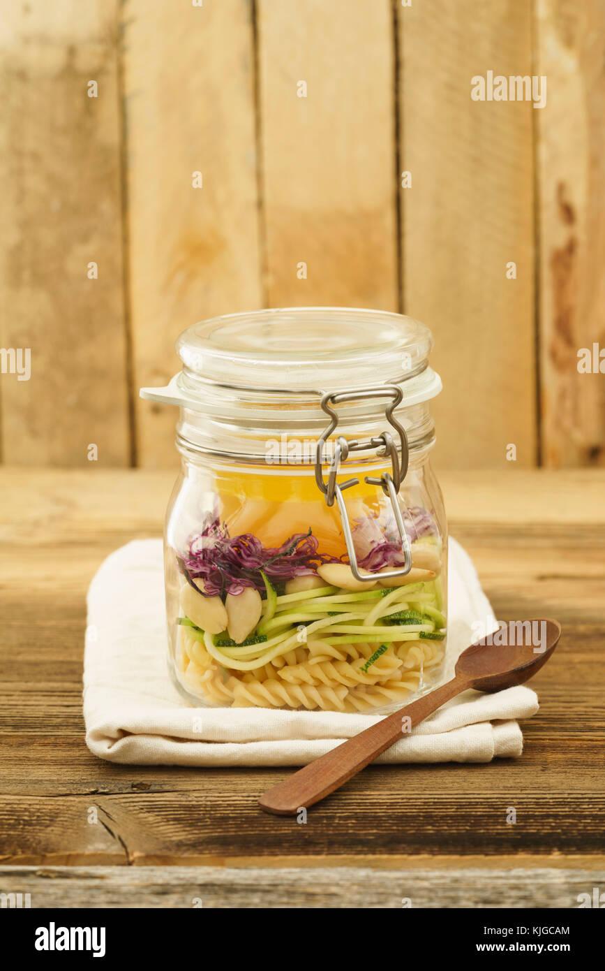 Veganer und vegetarischer Salat zum Mitnehmen im Glas mit Nudeln, spiralisierten Zucchini, Mandeln, Rotkohl und - Stock Image