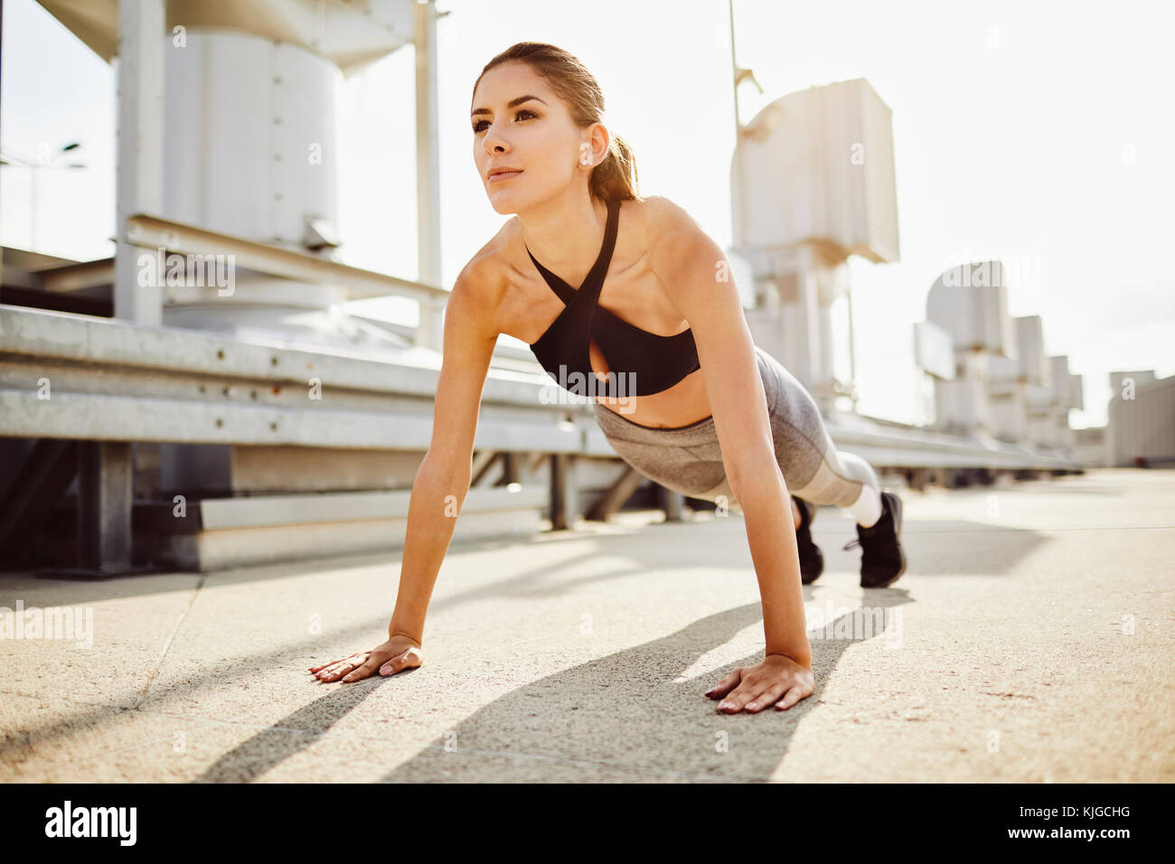 Young woman doing pushups in the city - Stock Image
