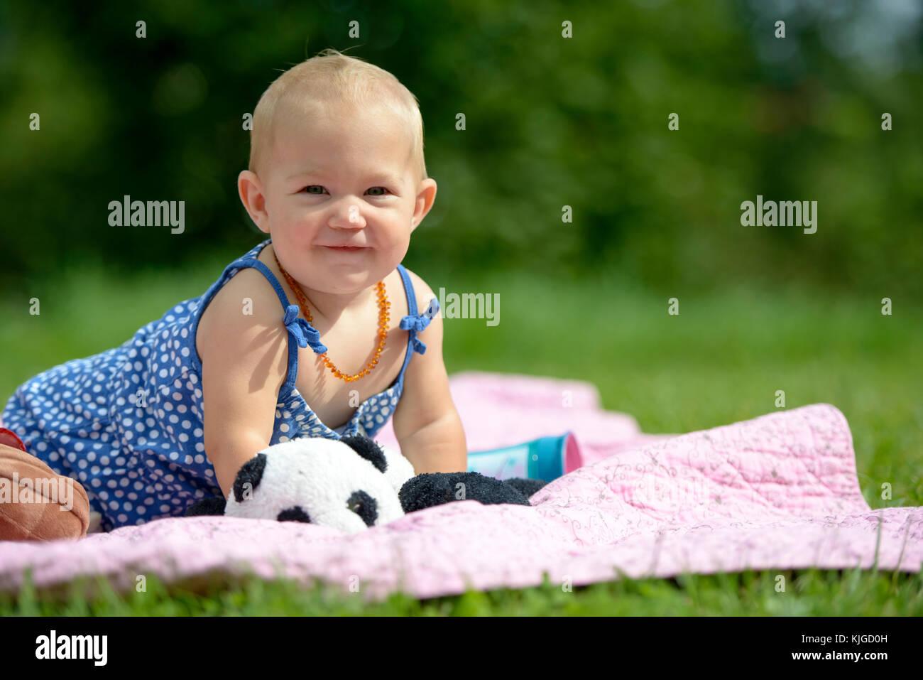 kleines Mädchen sitzt auf seiner Krabbeldecke im Grünen, Bayern, Deutschland - Stock Image
