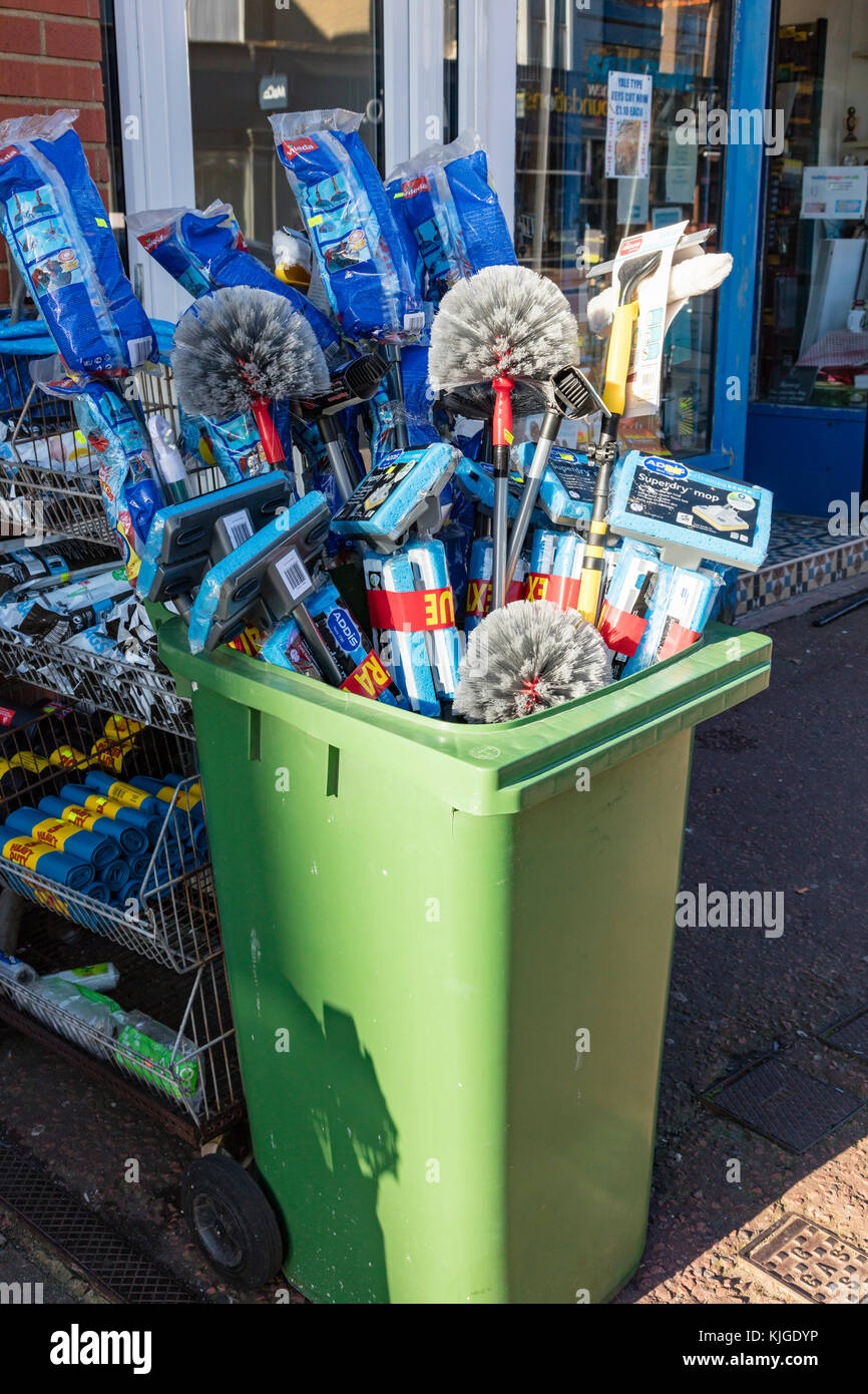 A collection of mops and brushes in a wheely bin outside an Ironmongers in Bexhill on Sea, East Sussex, UK - Stock Image