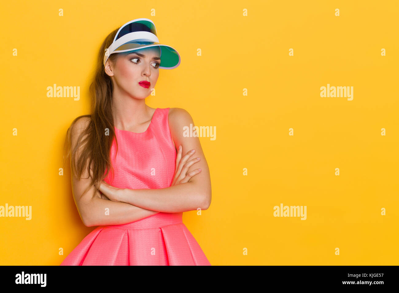 Grimacing young woman in pink dress and blue sun visor posing with arms crossed and looking away. Waist up studio - Stock Image