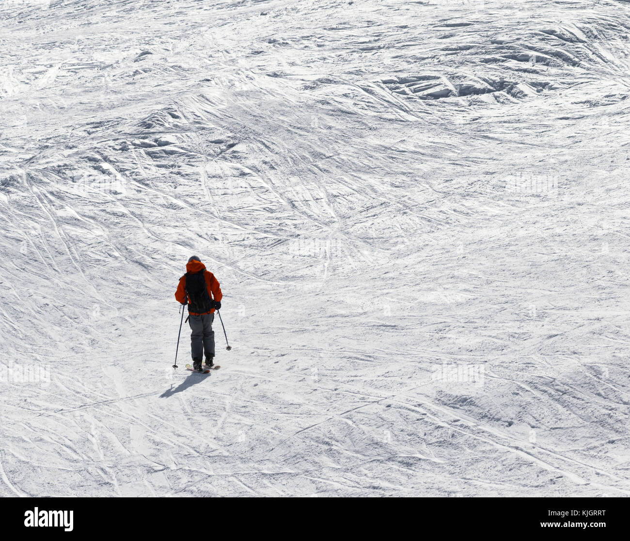 Skier downhill on snowy off-piste slope in sun winter day - Stock Image