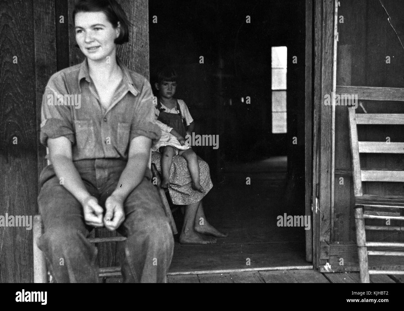 Black and white photograph of a depression era sharecroppers family woman sitting in a chair in the foreground a second woman holding two small children