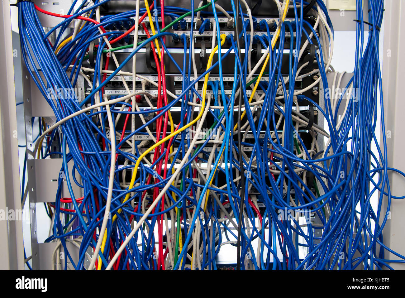 A computer network server cabinet with a mess of tangled blue coloured  cables. - Stock