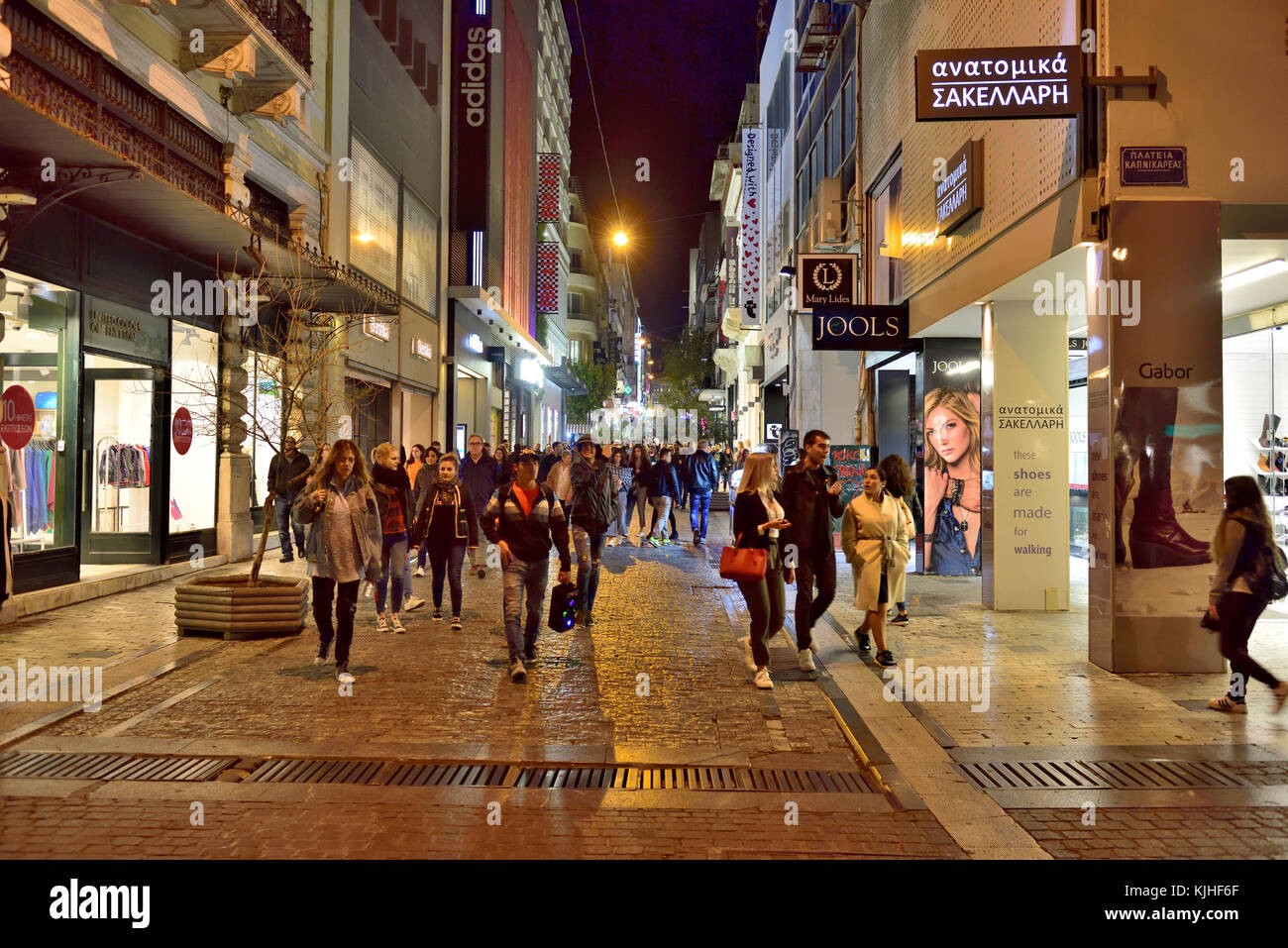 Night street life as people walk along Ermou street (one of the most popular shopping and socializing streets) in - Stock Image