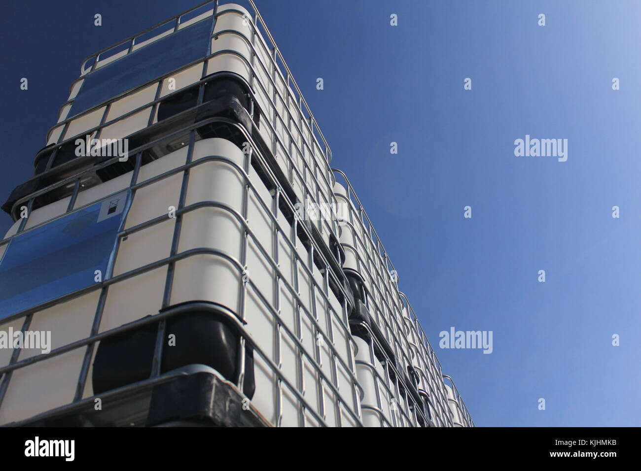 Stacked IBCs under the blue sky - Stock Image