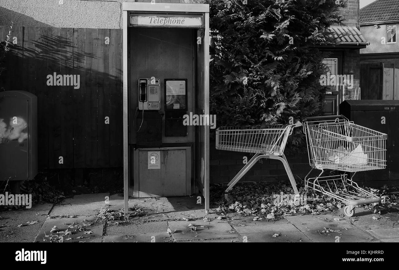 shopping trolley abandoned near phone box Stock Photo