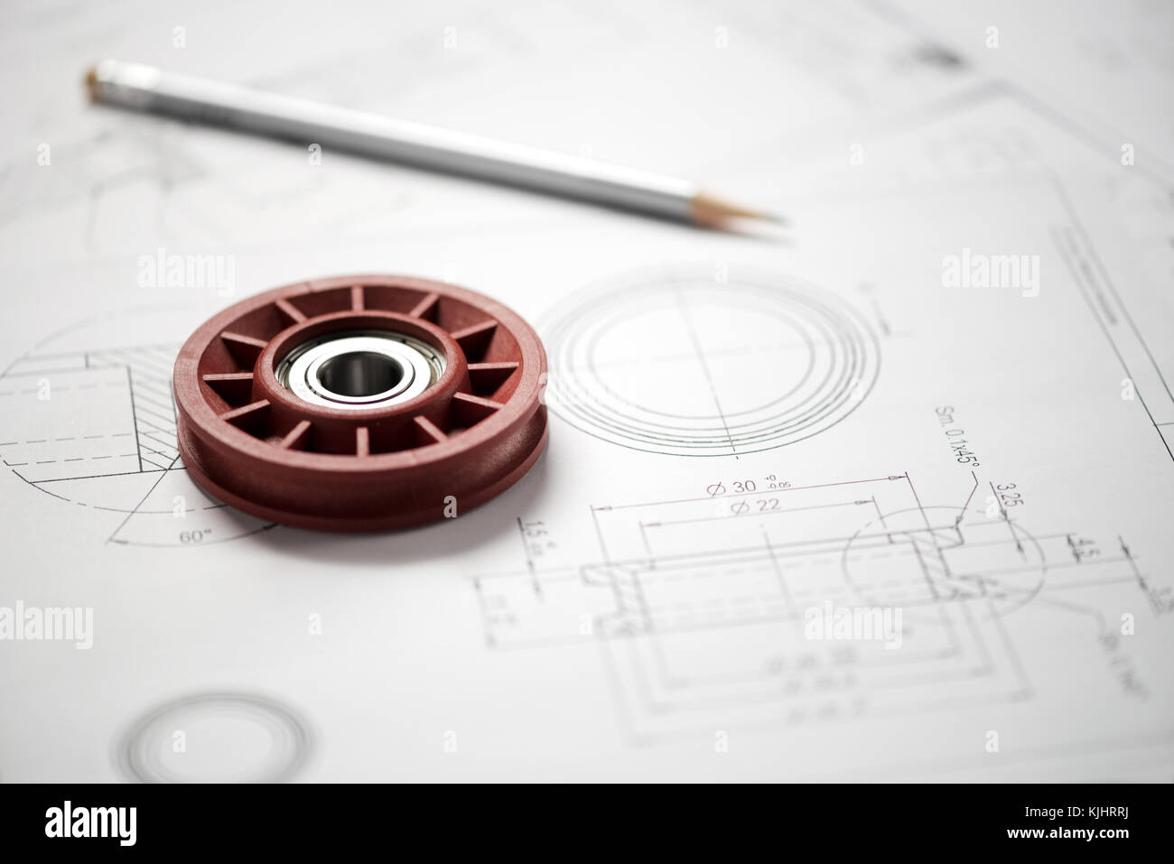 Plastic wheel bearing and grey pencil over blueprint with project drawings, close-up shot from high angle - Stock Image