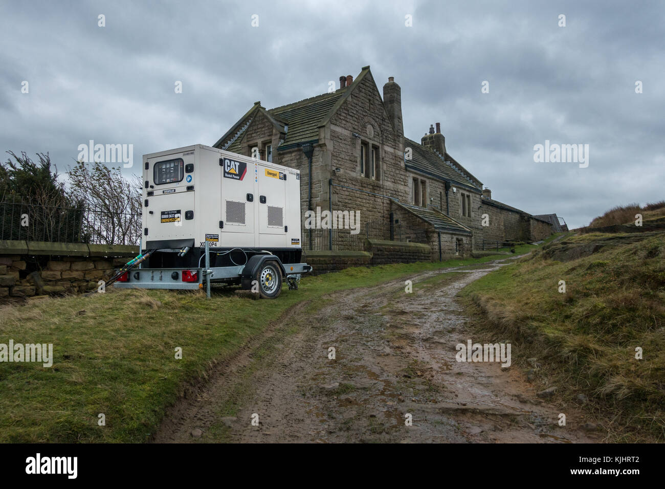 Cat Mobile Diesel Generator Set plugged in and running outside a rural countryside property having building work - Stock Image