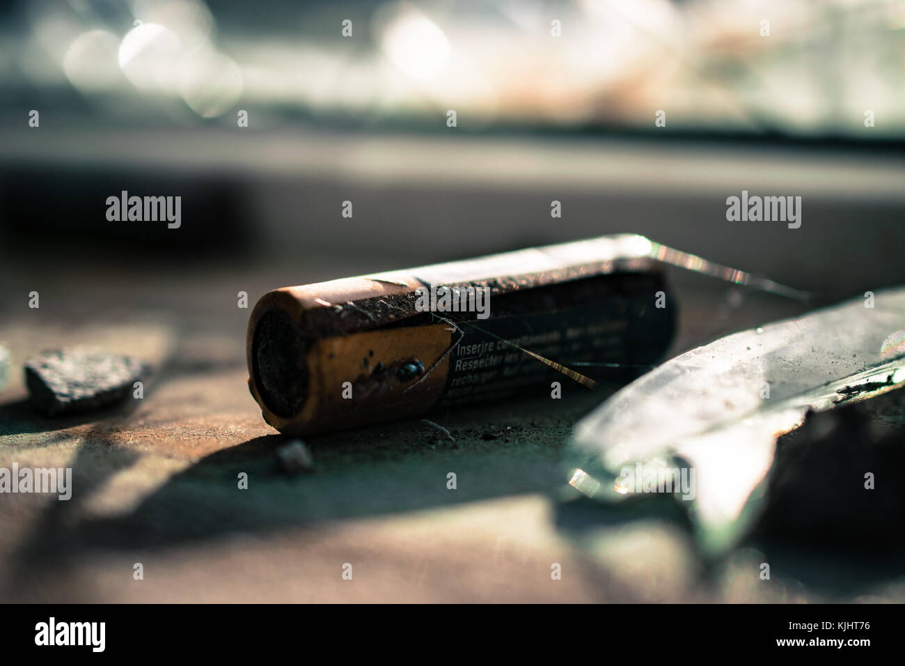 Abandoned battery on a windowsill. Battery rusted and corroded. - Stock Image