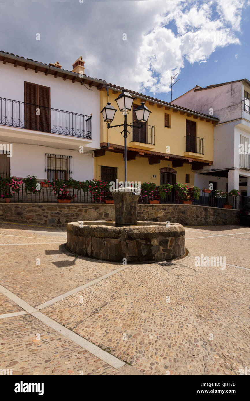 Fountain in the middle of a sunny lonely square in the village of Guadalupe, Extremadura, Spain - Stock Image