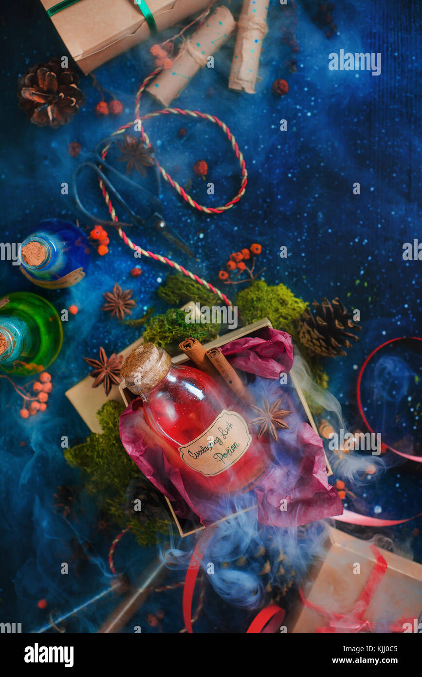 Gift box with a bottle of Luck Potion. Magical still life with potion bottles, ingredients and steam. Best wishes - Stock Image