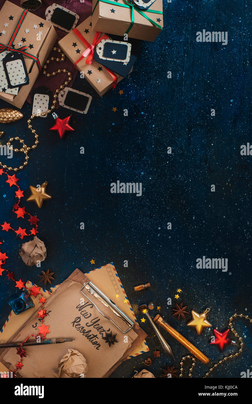 New Year resolution concept. Christmas celebration dark flat lay with presents, stars, craft paper boxes, tags, Stock Photo