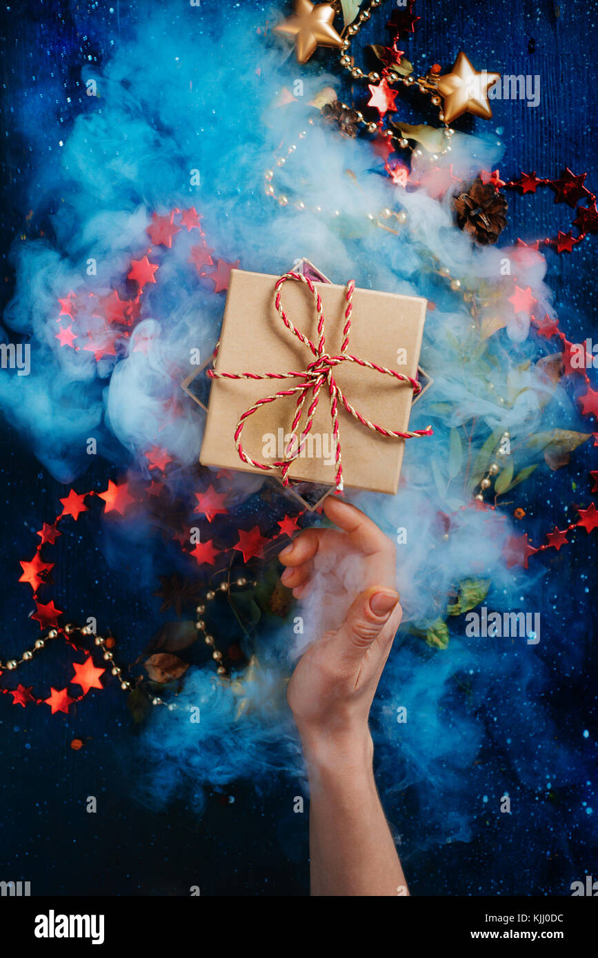 Christmas surprise concept, a gift box with dence steam and a reaching hand on a dark background with decorations - Stock Image