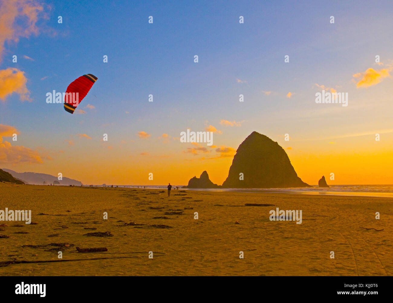 Kite flier on Cannon Beach with Haystack Rock at sunset on Oregon coast. - Stock Image