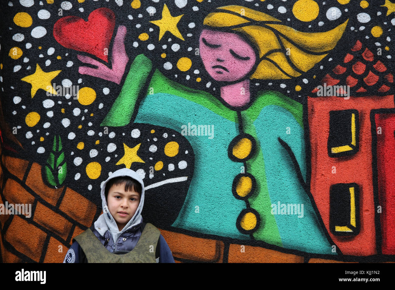 Boy standing by wall art. France. - Stock Image