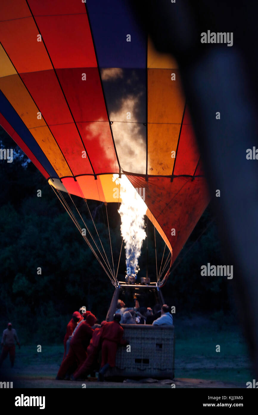 A gas jet flame fills a hot air balloon at dawn for a tourist flight over the African savanna. Masai Mara game reserve. - Stock Image