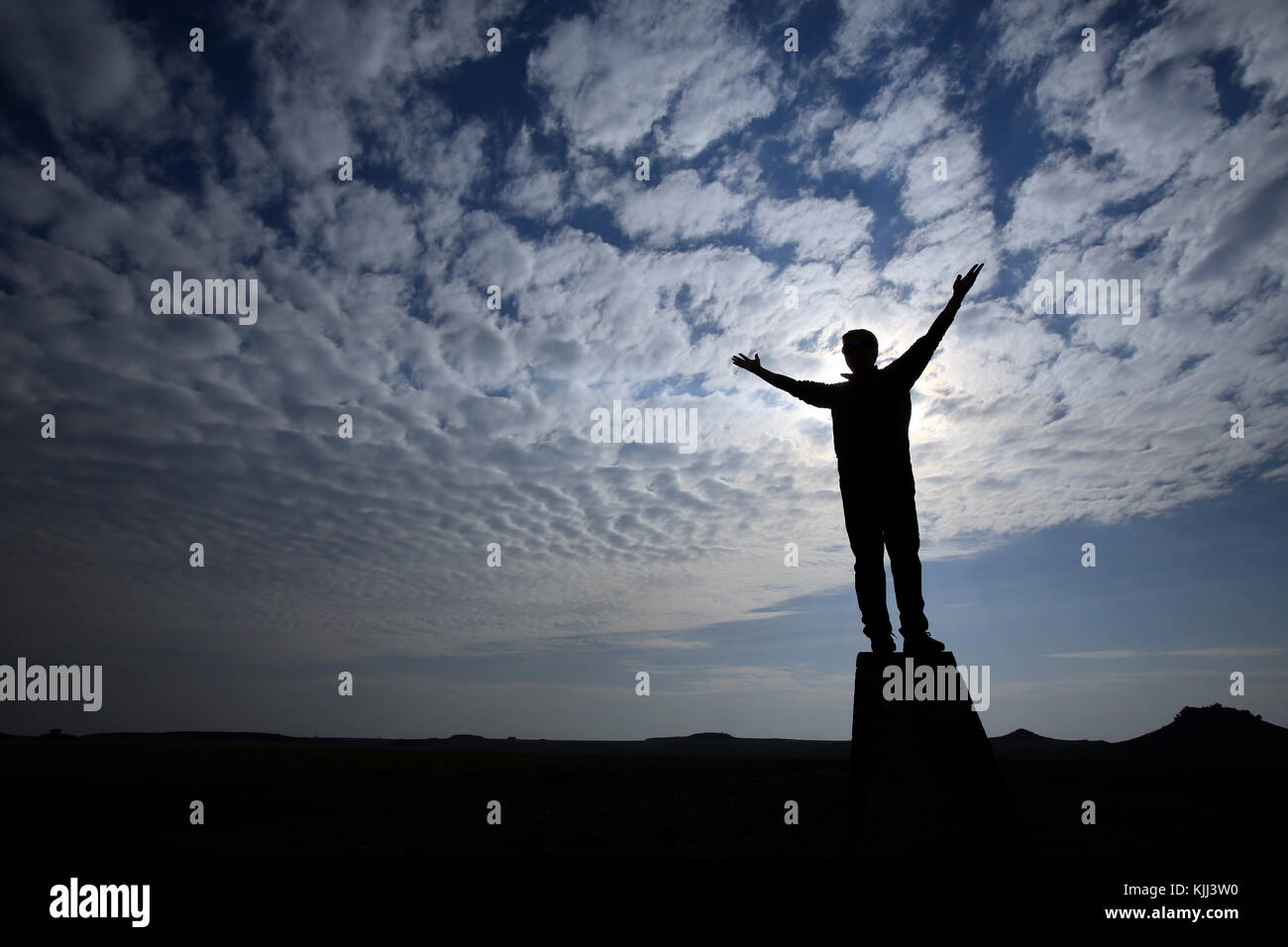 Man with arms raised praying against cloudy sky. Silhouette. - Stock Image