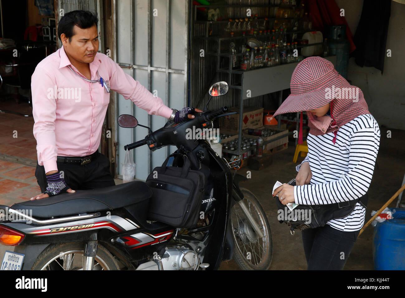 Microfinance institution employee gazing up in Battambang. Cambodia. - Stock Image