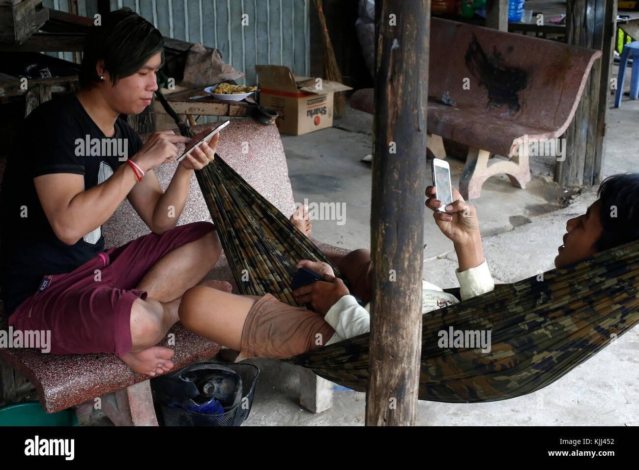 Young Khmers using cell phones. Battambang.  Cambodia. - Stock Image