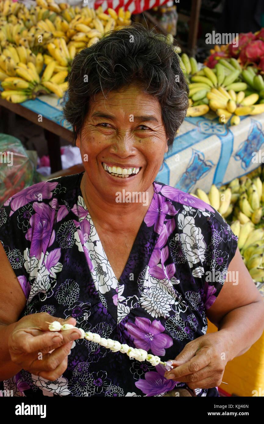 Woman making a garland at a Battambang market. Cambodia. - Stock Image