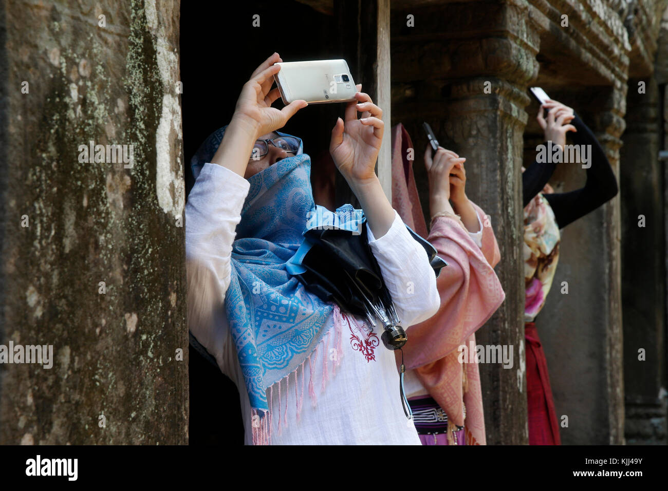 Angkor temple complex. Tourists taking photographs with cell phones. Cambodia. - Stock Image