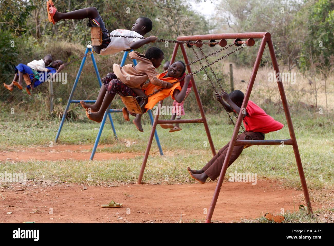 Ugandan children on swings. Uganda - Stock Image