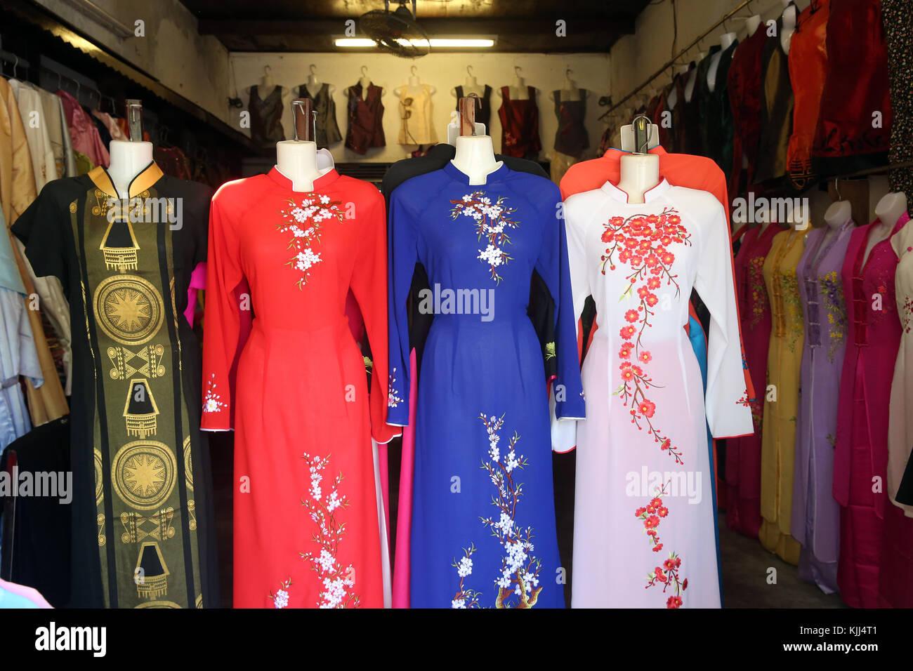 Vietnamese shop front selling traditional women's dress: the Ao Dai. Hoi An. Vietnam. - Stock Image