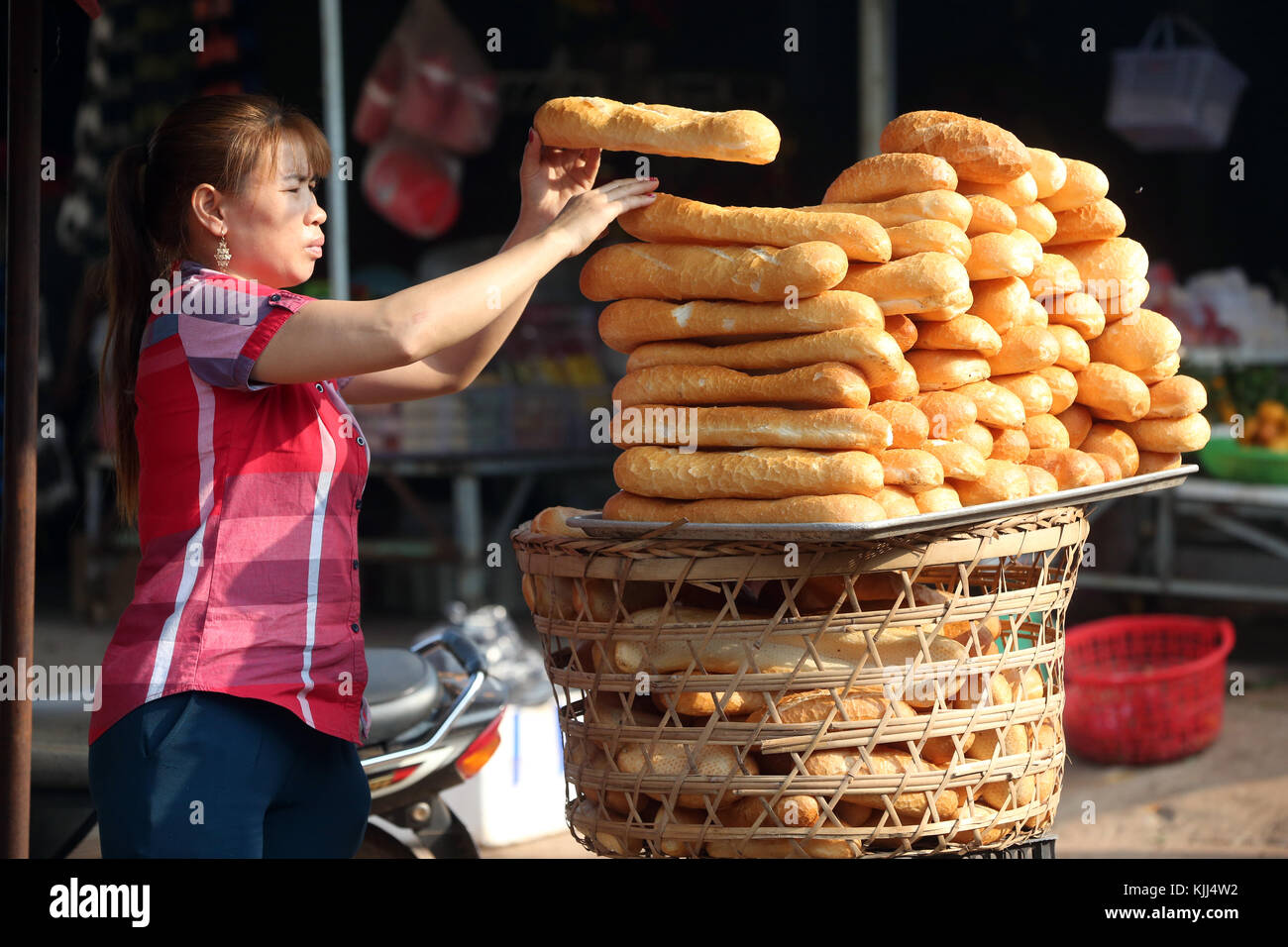 Woman selling french style bred in market.  Thay Ninh. Vietnam. - Stock Image