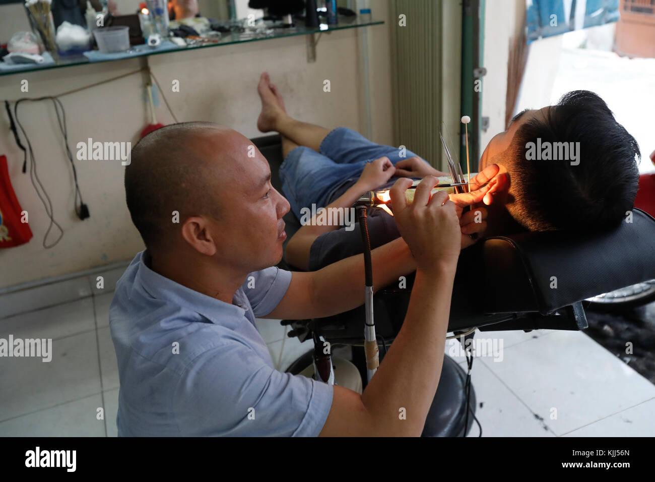 Vietnamese barber shop. Ear cleaning.  Ho Chi Minh City. Vietnam. - Stock Image