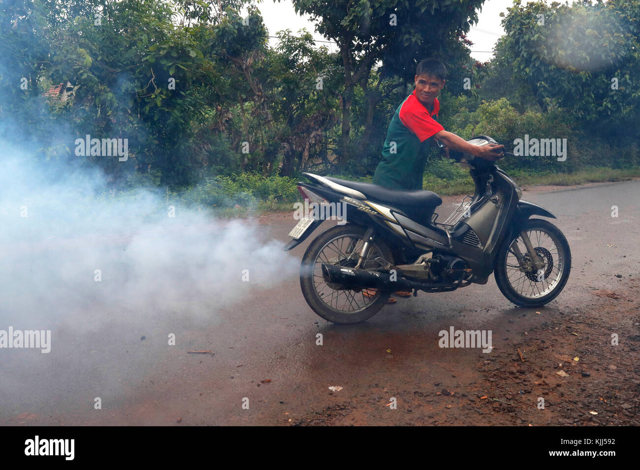 Motorbike smoke. Air pollution.  Kon Tum. Vietnam. - Stock Image