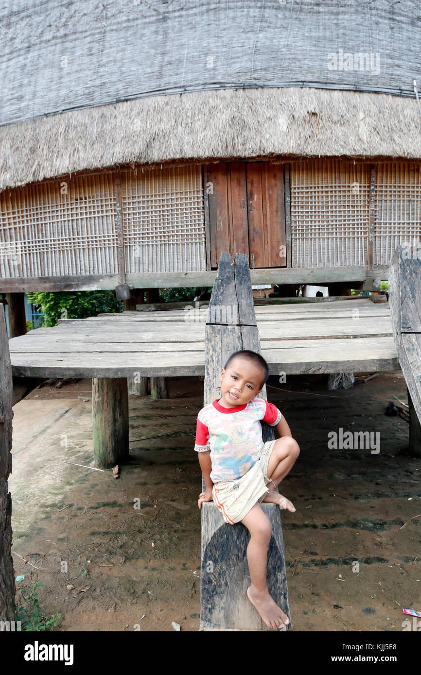 Bahnar ethnic minority people's communal Rong house. Young boy.  Kon Tum. Vietnam. - Stock Image