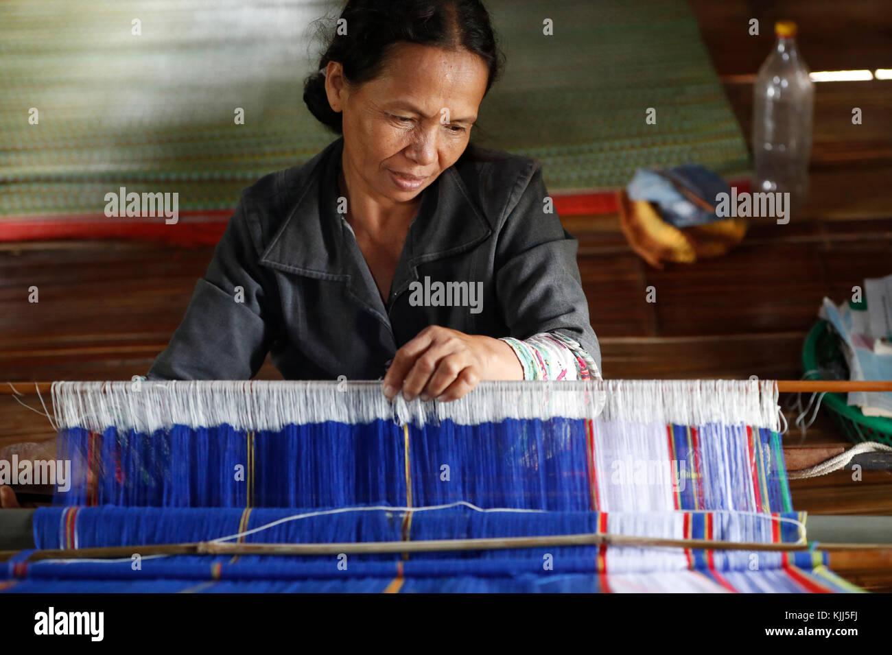 Bahnar (Ba Na) ethnic group.  Woman weaving silk at wooden loom.  Kon Tum. Vietnam. - Stock Image