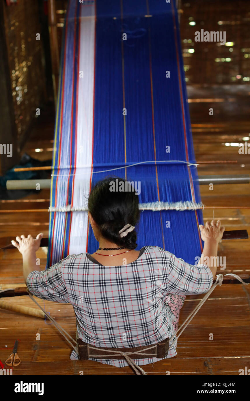 Bahnar (Ba Na) ethnic group.  Woman weaving silk at wooden loom.  Kon Tum. Vietnam. - Stock Image
