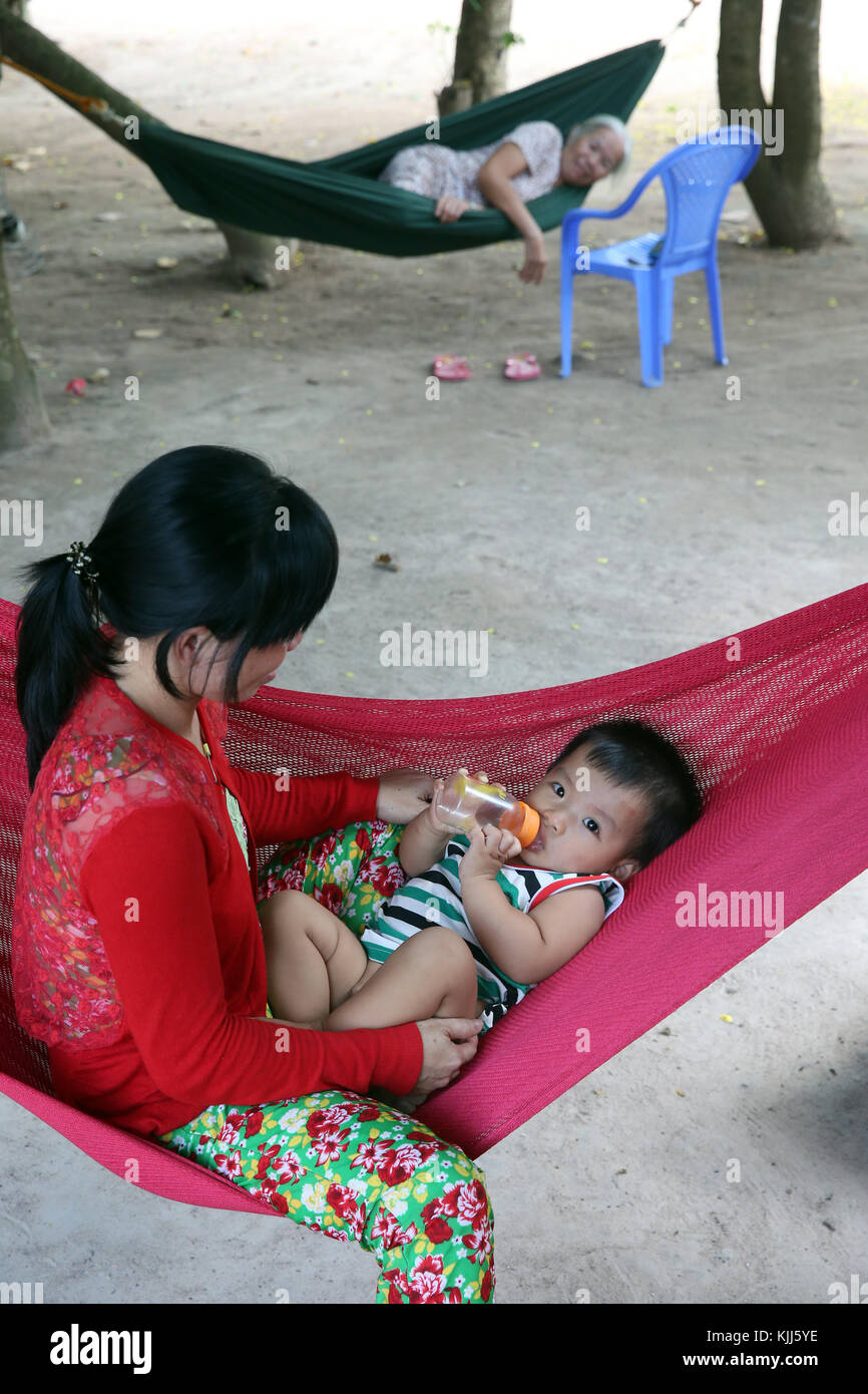 Mother and child relaxing in hammock. Thay Ninh. Vietnam. - Stock Image