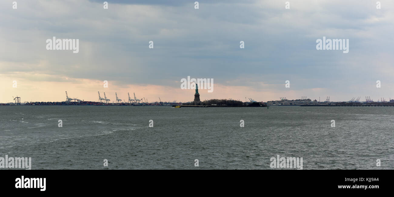 View of the Statue of Liberty over the water with cargo crains in the distance. Stock Photo