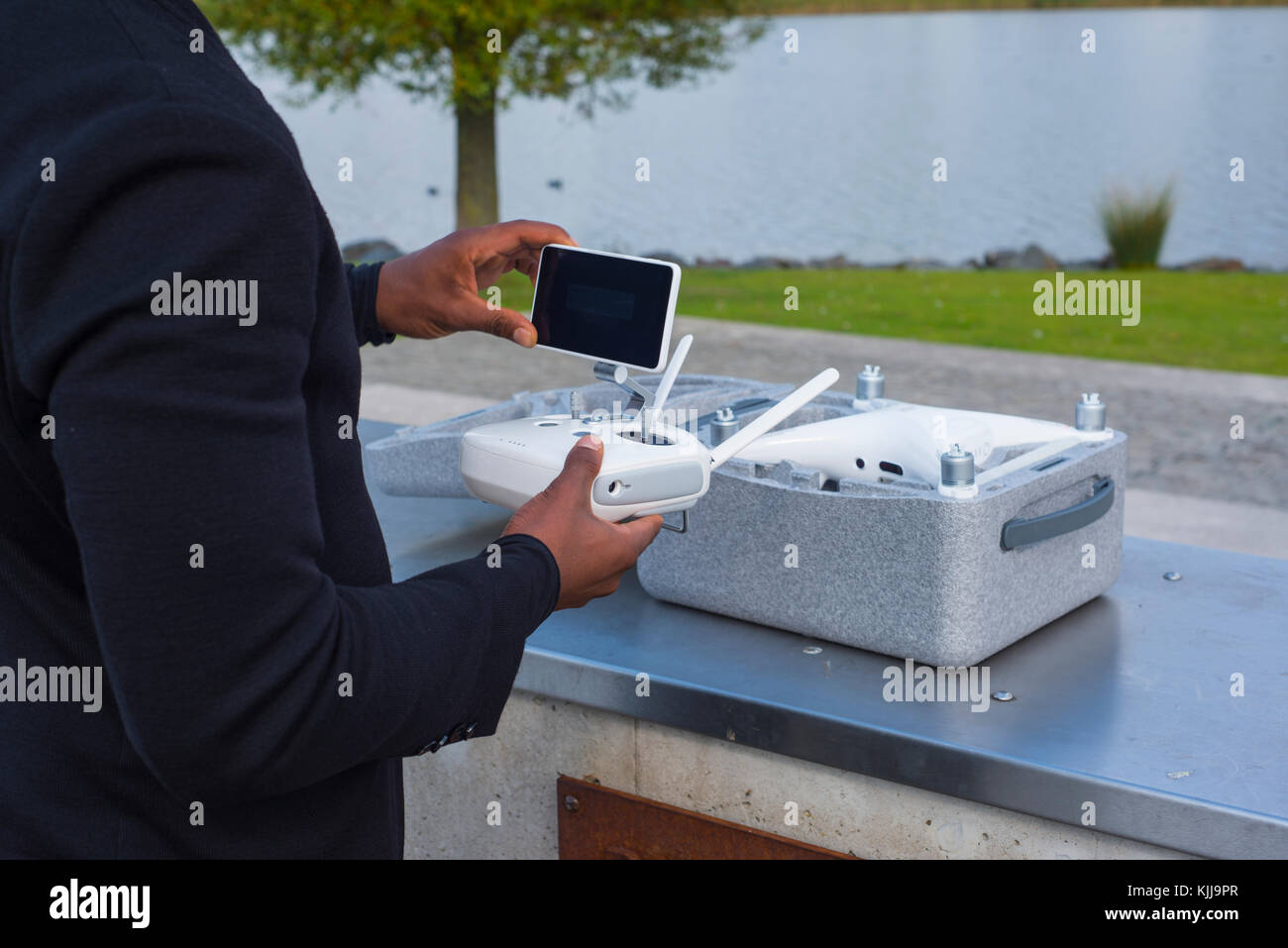 Drone equipment near a lake and the drone box delivered package - Stock Image