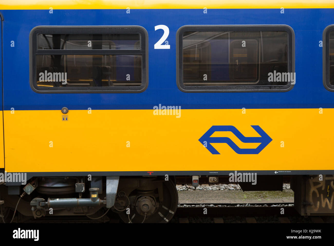 A train on the track at Groningen, in the Netherlands. It bears the yellow and blue livery of the Nederlandse Spoorwegen - Stock Image
