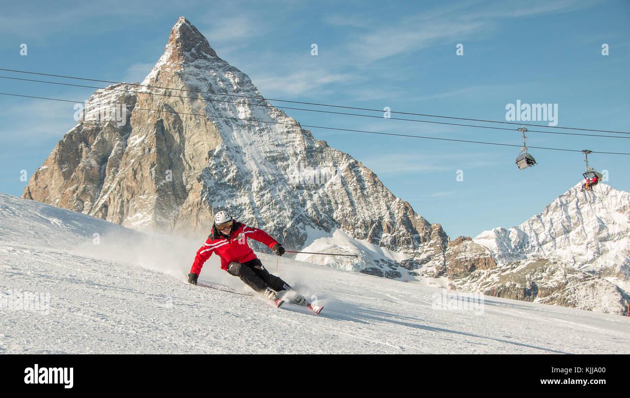 A man ski instructor skiing in front of the Matterhorn mountain of Zermatt ski resort of Switzerland red jacket - Stock Image