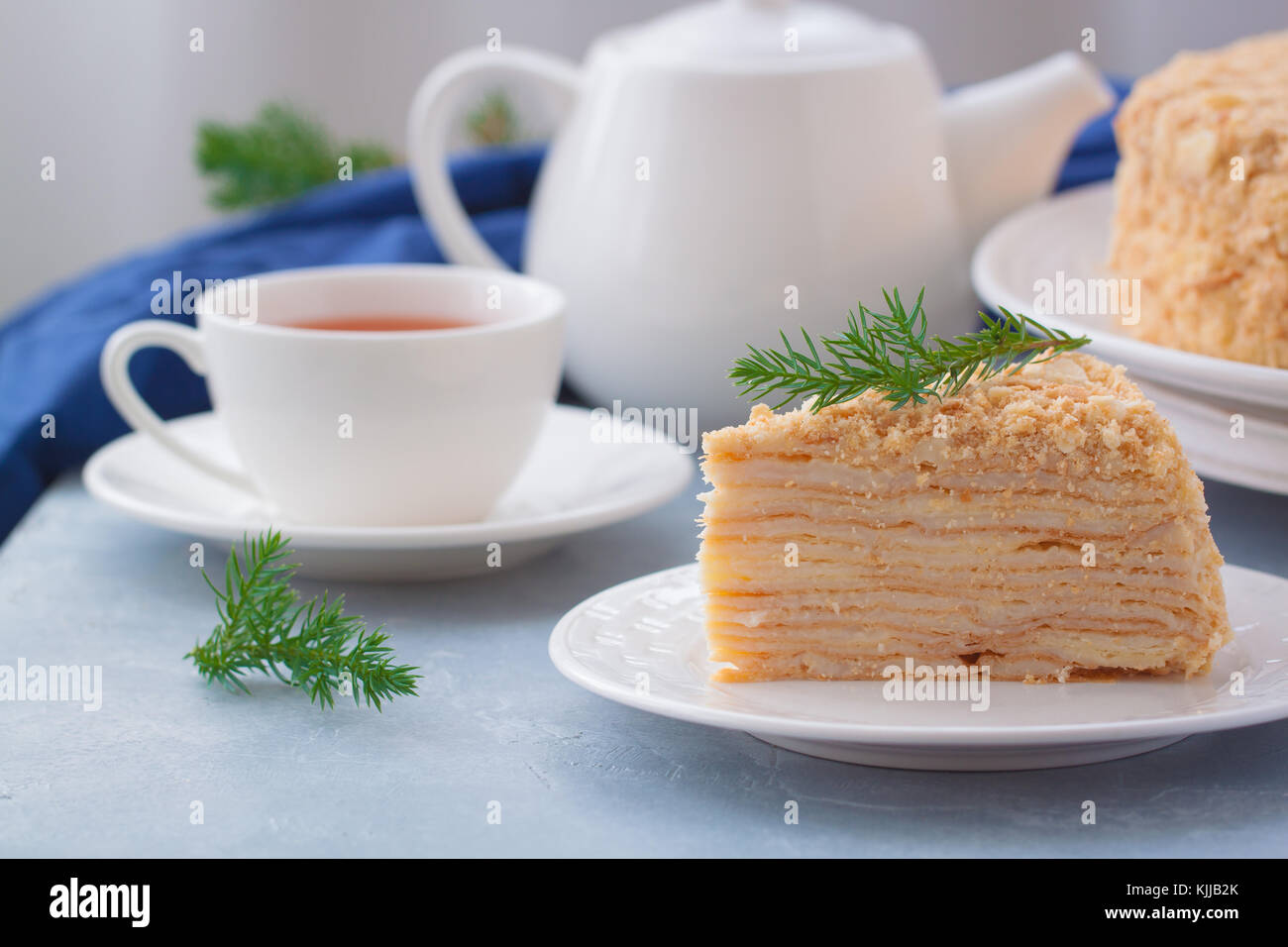 Round multi-layered cake Napoleon with custard, on a light-blue table background. Selective focus. Russian cuisine. - Stock Image