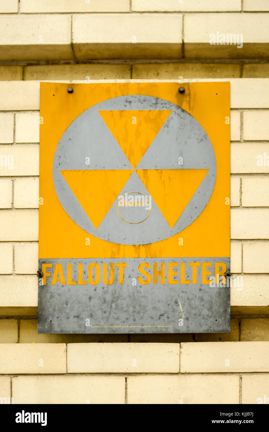 Atomic nuclear fallout shelter sign with radiation symbol on a brick wall. Stock Photo