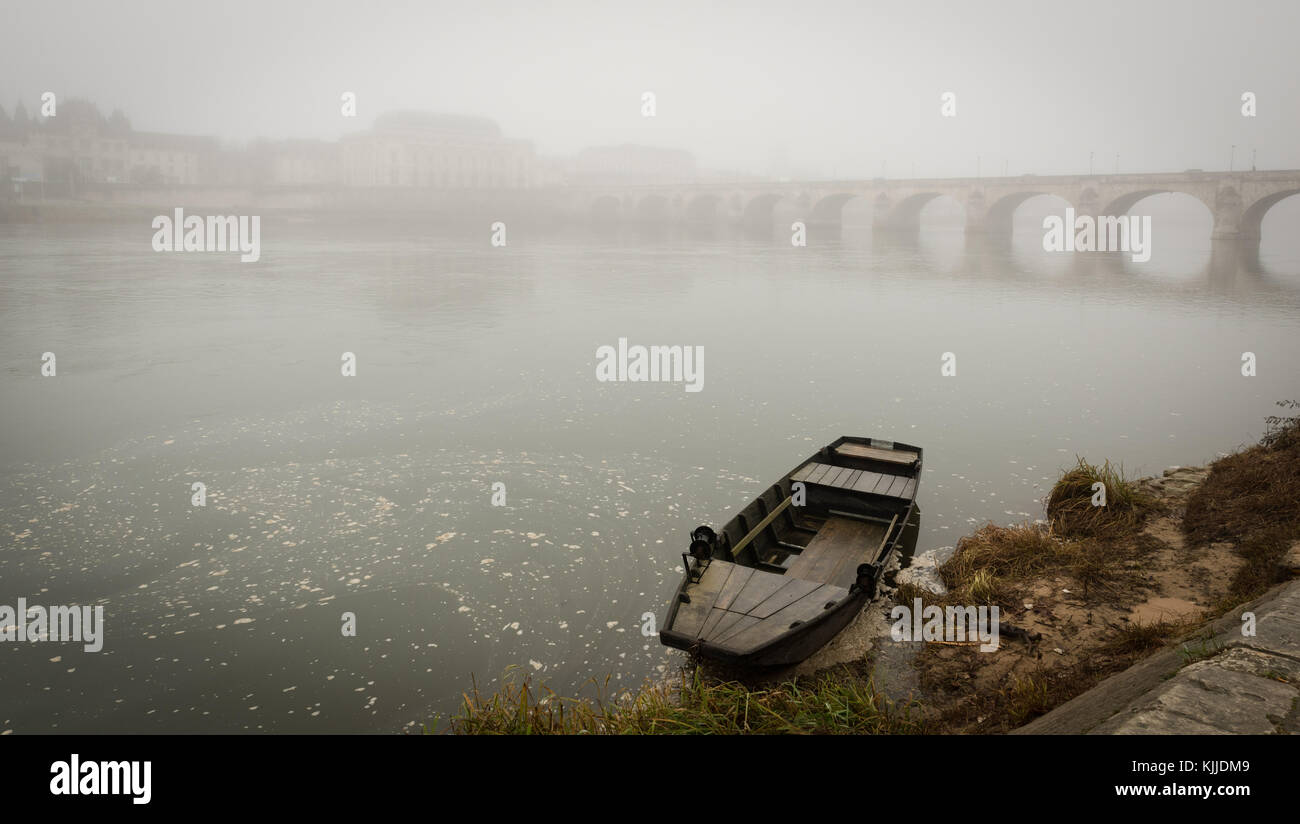 'Toue' fishing boat anchored on the Loire river in front of a misty city view of Saumur, with bridge - Stock Image