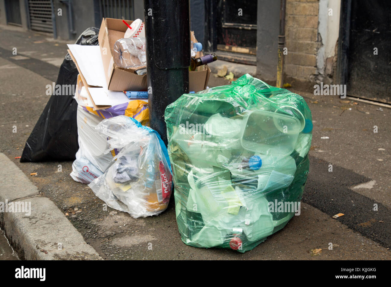 London, England, November 2017, Bags of rubbish in different colour sacks await collection on the street - Stock Image